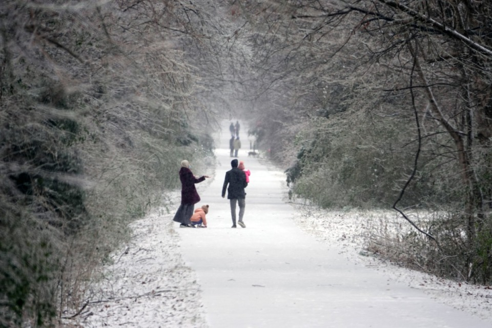 <strong>A family plays in the snow along the Greenline in Cordova on Sunday afternoon Feb. 14, 2021.</strong> (Karen Pulfer Focht/Special to Daily Memphian)