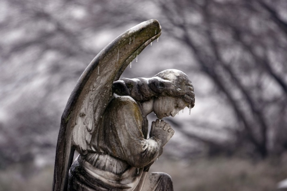<strong>Icicles drip from a frozen angel in prayer at Elmwood Cemetery in Memphis on Saturday, Feb. 13, 2021.</strong> (Karen Pulfer Focht/Special to Daily Memphian)