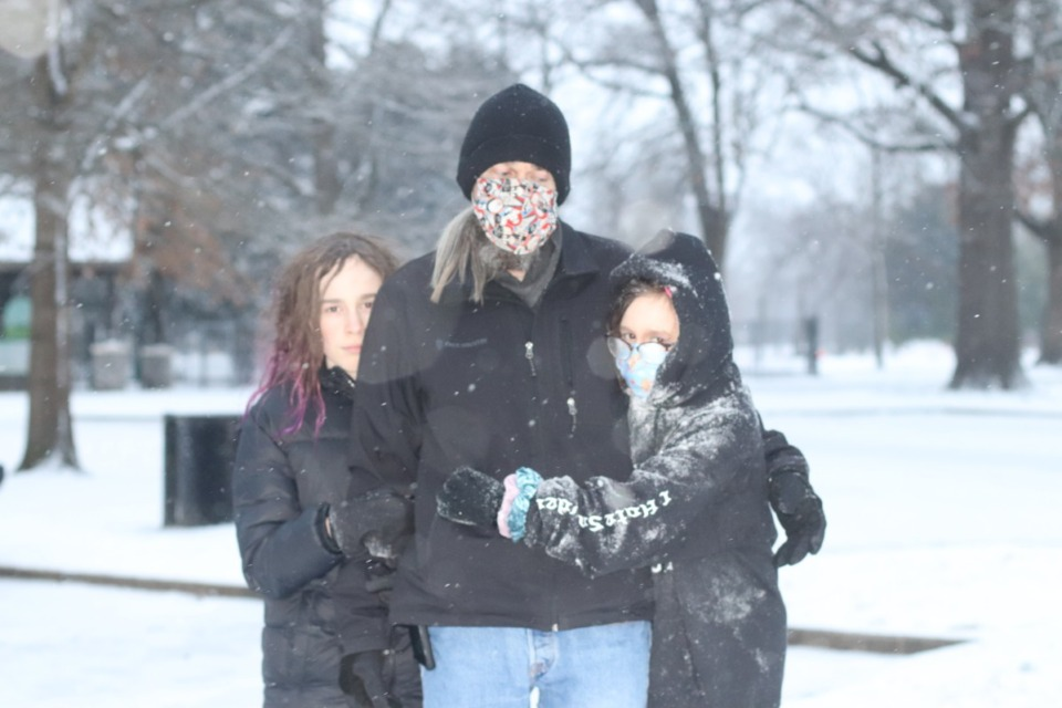 <strong>Dale Childress and his children Thompson (left) and Evelyn (right) headed to Overton Park to sled down the hill at Levitt Shell.</strong> (Daja E. Henry/Daily Memphian)