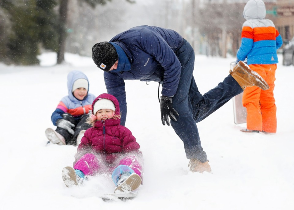 <strong>Waverly McKenna, 6 (bottom) gets a push form her father Mike McKenna sledding during heavy snow storm on Monday, Feb. 15, 2021.</strong> (Mark Weber/The Daily Memphian)