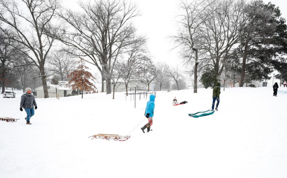 <strong>Sledders head up a hill during a heavy snow storm in Overton Park on Monday, Feb. 15, 2021.</strong> (Mark Weber/The Daily Memphian)