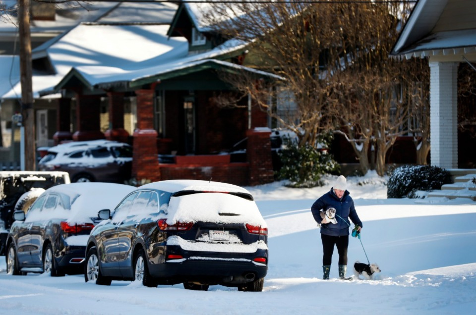 <strong>While walking her dogs, a woman slowly makes her way over snow covered sidewalks on Tuesday, Feb. 16, 2021. City officials have advised that driving will be difficult until roads are cleared.</strong> (Mark Weber/The Daily Memphian)
