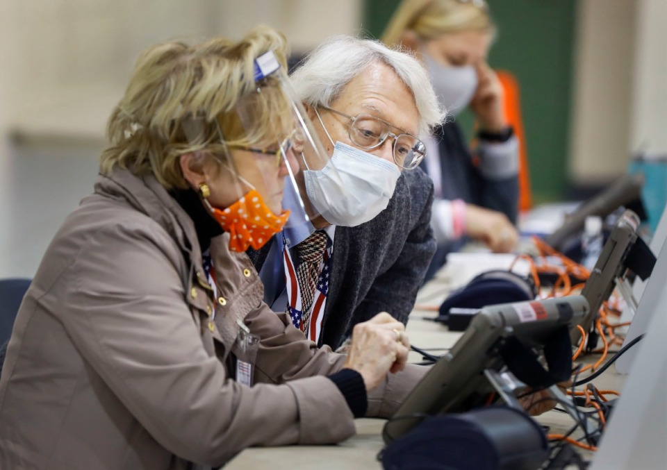 <strong>Poll worker Bruce Smedley (middle) helps to verify voters on Tuesday, Nov. 3, 2020, at the Lester Community Center.</strong> (Mark Weber/The Daily Memphian)