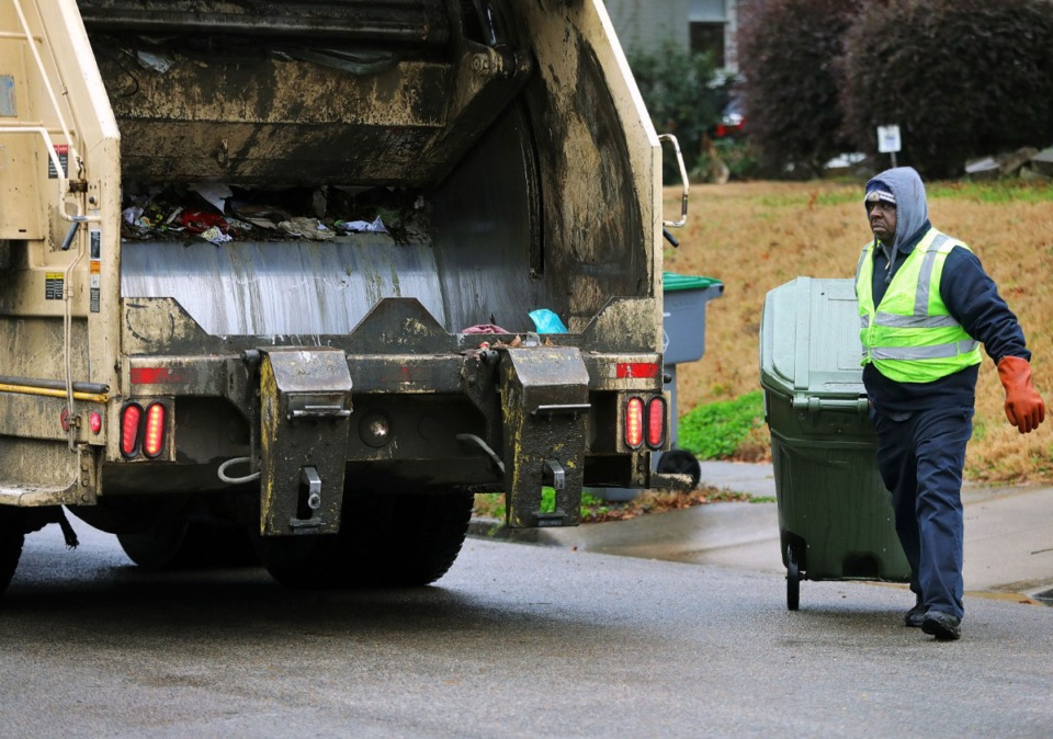 <strong>A sanitation worker hauls a garbage can to his truck in the Evergreen neighborhood of Midtown, Memphis Jan. 31, 2020. Sanitation in Collierville will be delayed one week, but residents can utilize the transfer station this weekend to dispose of excess garbage.</strong> (Patrick Lantrip/Daily Memphian file)