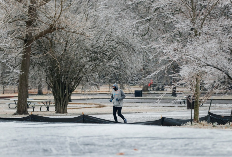 <strong>Surrounded by icy trees, a runner makes his way through Overton Park on Thursday, Feb. 11, 2021, after freezing rain fell over night.</strong> (Mark Weber/The Daily Memphian)