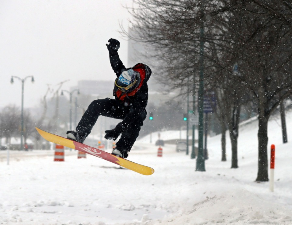 <strong>Beau Bowden grabs his snowboard while catching air at the bottom of the Mississippi River Bluffs in Downtown Memphis on Wednesday, Feb. 17.</strong> (Patrick Lantrip/Daily Memphian)