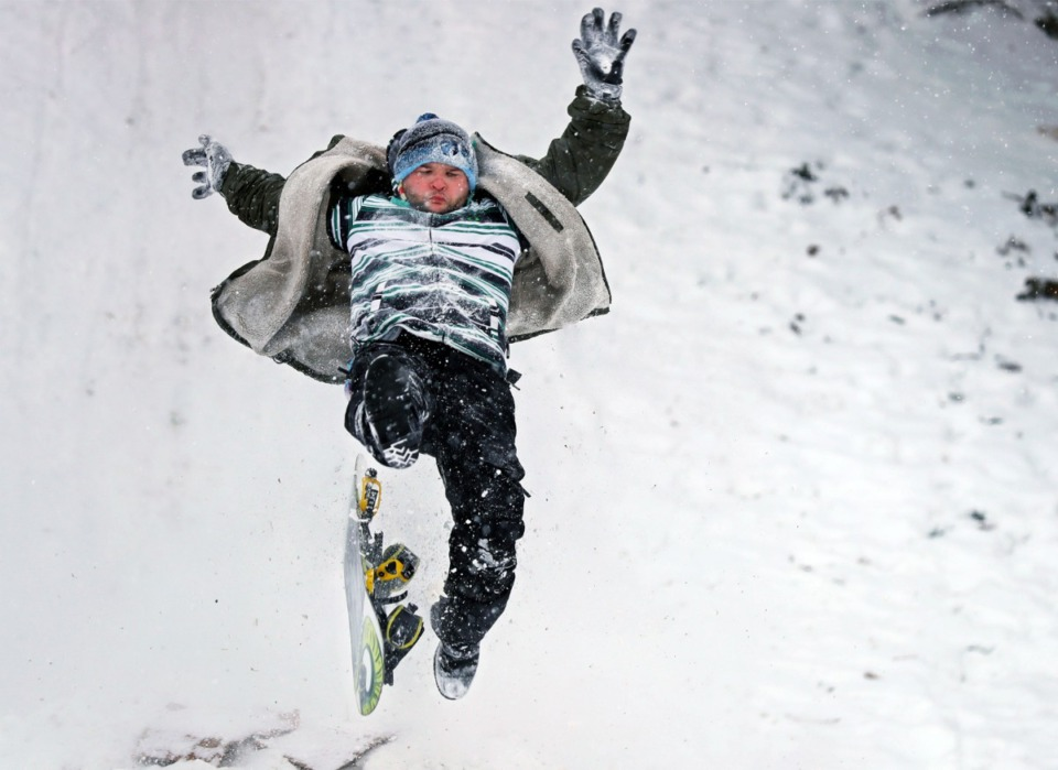<strong>Carl Harrell slips off his snowboard as it comes off a ramp at the bottom of the Mississippi River Bluffs in Downtown Memphis on Wednesday, Feb. 17.</strong> (Patrick Lantrip/Daily Memphian)