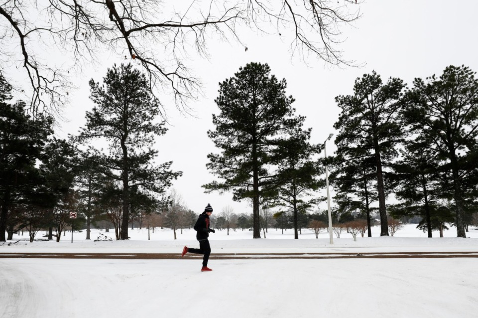 <strong>Spencer Moore runs along Walnut Bend Road in a winter wonderland on Wednesday, Feb. 17, 2021.</strong> (Mark Weber/The Daily Memphian)