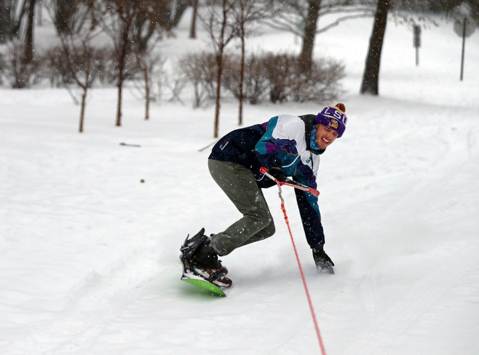 <strong>Eric Andries tries to maintain his balance on a snowboard while being dragged behind his friend's truck in Overton Park on Wednesday, Feb. 17.</strong> (Patrick Lantrip/Daily Memphian)