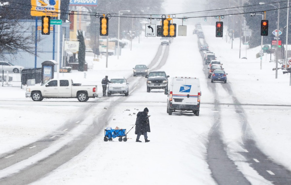 <strong>As snow falls, a woman carries her groceries in a wagon across Poplar Avenue on Wednesday, Feb. 17.</strong> (Mark Weber/Daily Memphian)