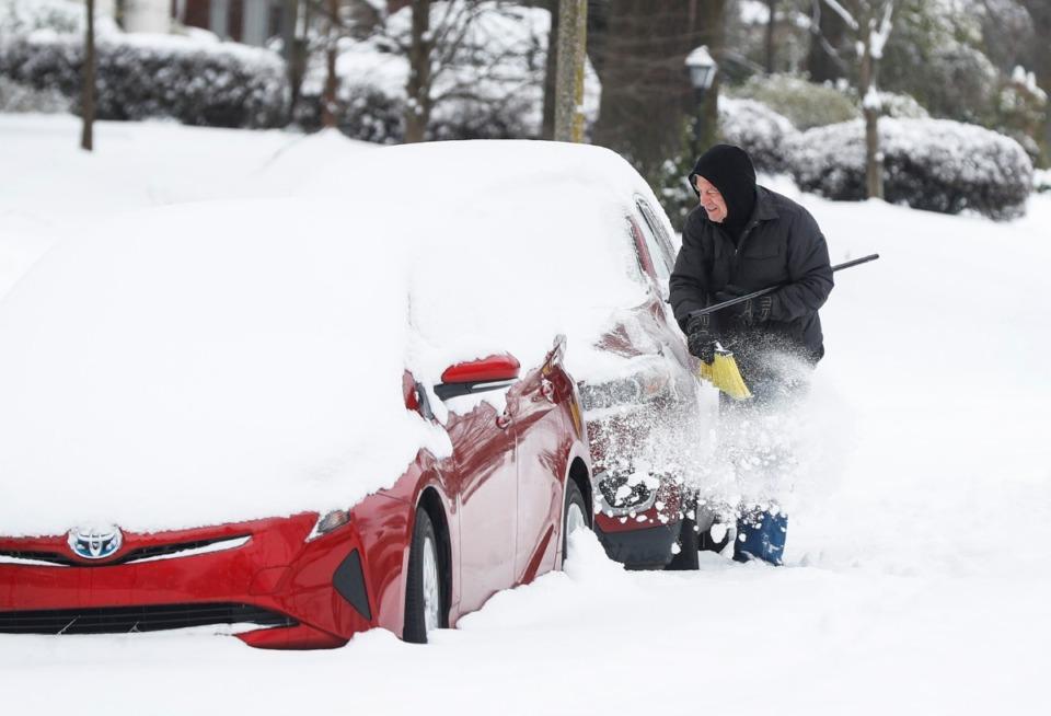 <strong>A man uses a broom to clear snow from his car on Thursday, Feb. 18, 2021.</strong> (Mark Weber/The Daily Memphian)