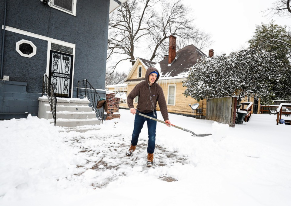 <strong>Brian Sheridan shovels snow in the driveway of his new home, to make way for moving trucks on Thursday, Feb. 18, 2021.</strong> (Mark Weber/The Daily Memphian)