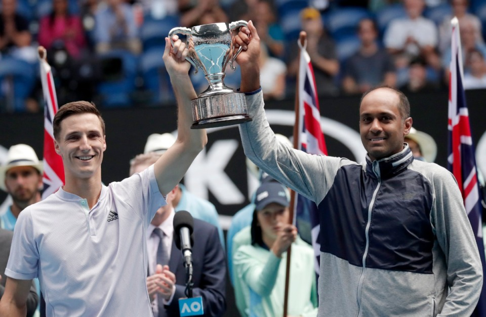 <strong>Britain's Joe Salisbury (left) and partner Rajeev Ram of the U.S. hold their trophy aloft after winning the men's doubles final at the Australian Open tennis championship on Feb. 2, 2020. On Saturday, Feb. 20, the two will defend their title.</strong> (Lee Jin-man/Associated Press file)