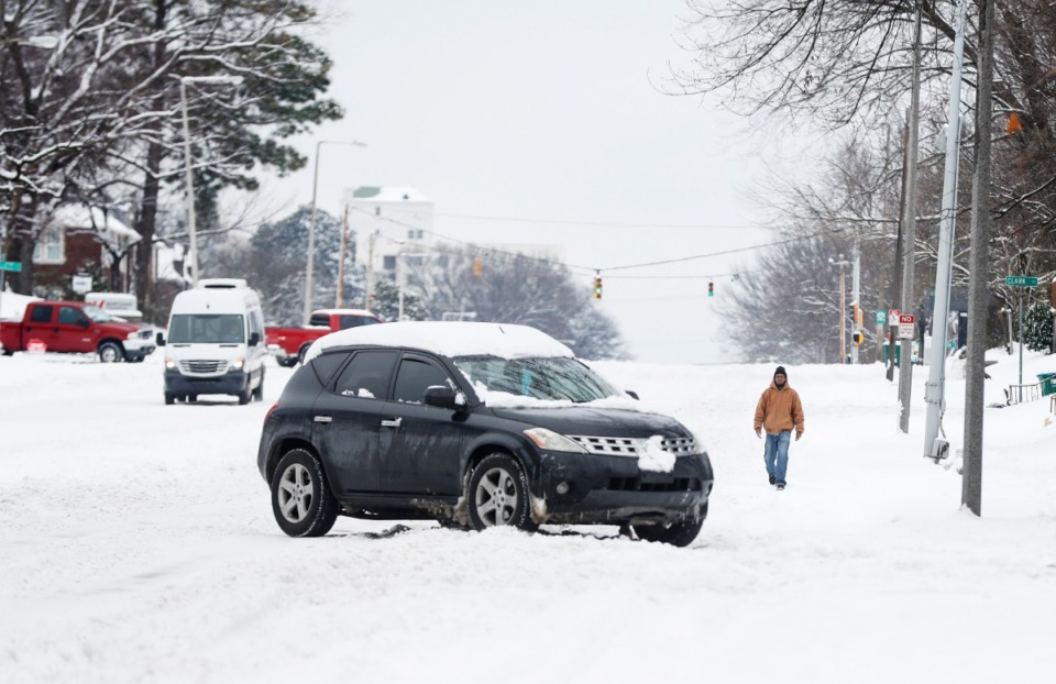 <strong>Cars on Poplar Avenue had to negotiate deep snow on Thursday, Feb. 18, 2021. Memphis Public Works will begin plowing collector streets this weekend.</strong> (Mark Weber/The Daily Memphian)