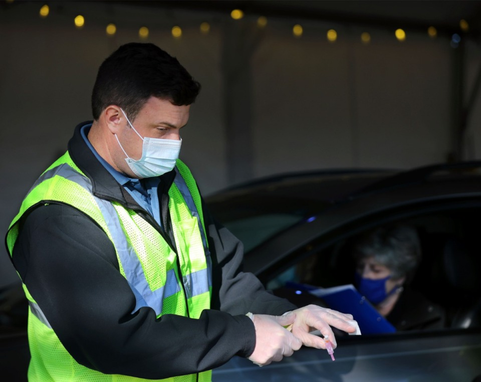<strong>Reece Halyard with the Collierville Fire Department gets a COVID-19 vaccine ready at Germantown Baptist Church's drive-thru location Feb. 2, 2021.</strong> (Patrick Lantrip/Daily Memphian)