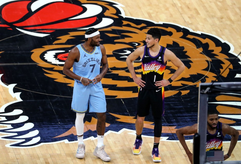 <strong>Memphis Grizzlies forward Justise Winslow (7) shares a laugh with Phoenix Suns guard Devin Booker (1) after checking into a Feb. 20, 2021 game at the FedExForum.</strong> (Patrick Lantrip/Daily Memphian)
