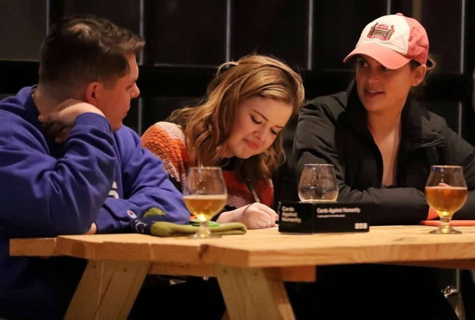 <strong>Noah Connor, Caroline Cullum and Mary Jane Hedden try to name the tune during music trivia at Crosstown Brewing on Wednesday, Jan. 9, 2019.</strong> (Patrick Lantrip/Daily Memphian)