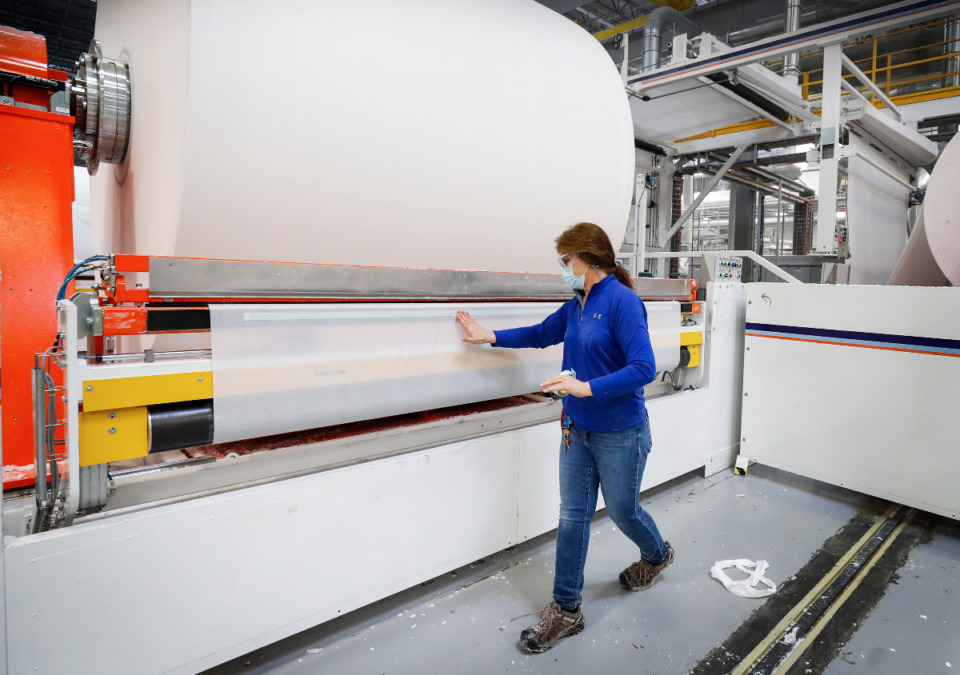 <strong>Kruger Products employee Lorie Painter prepares a parent roll of paper that will be merged with another roll to make two-ply paper on Tuesday, Feb. 23, 2021.</strong> (Mark Weber/The Daily Memphian)