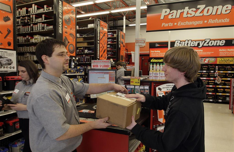 <strong>Autozone employee Timothy Spina, left, hands a part to customer Taylor House at the Autozone retail store at 7699 W. Farmington in Germantown.</strong>&nbsp;(Photo by Lance Murphey)