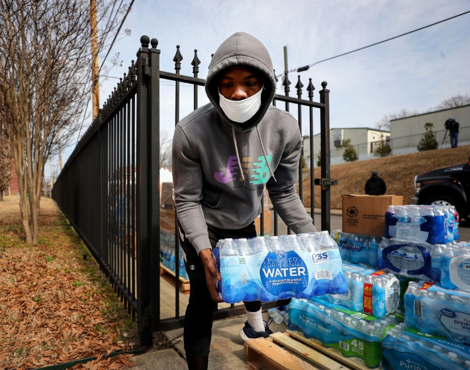 <strong>Antwain Booker helps unload cases of bottled water from Chicago donated to LeMoyne-Owen College Feb. 25, 2021.</strong> (Patrick Lantrip/Daily Memphian)