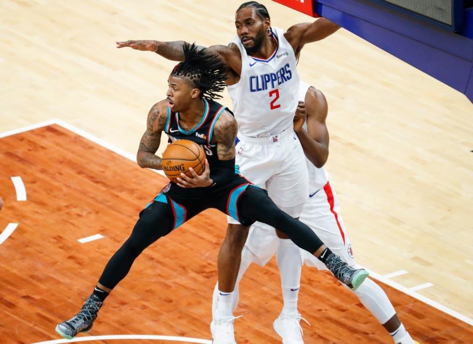 <strong>Memphis Grizzlies guard Ja Morant (left) makes a pass in front of Clipper Kawhi Leonard (right) on Thursday, Feb. 25, 2021.</strong> (Mark Weber/The Daily Memphian)