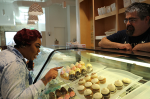 <strong>Tameica Couch picks out a pastry at Lucy J's Bakery with the help of co-owner Josh Burgess Thursday, Jan. 10. Burgess has committed to paying all of his employees at least $15 an hour, a price that many consider the minimum living wage.</strong> (Patrick Lantrip/Daily Memphian)