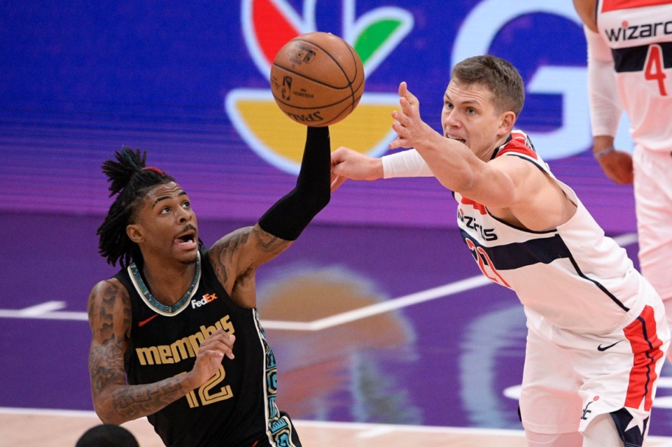 <strong>Grizzlies guard Ja Morant (12) and Washington Wizards center Moritz Wagner (21) reach for the ball on March 2 in Washington. Morant finished with 35 points.</strong> (Nick Wass/AP)