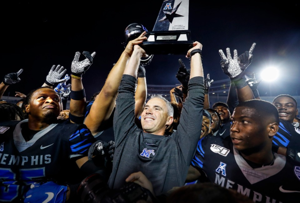 <strong>Former Memphis head coach Mike Norvell (middle) raises the AAC Western Divisional Champion Trophy after defeating Cincinnati Friday, Nov. 29, 2019 at the Liberty Bowl Memorial Stadium.</strong> (Mark Weber/Daily Memphian file)