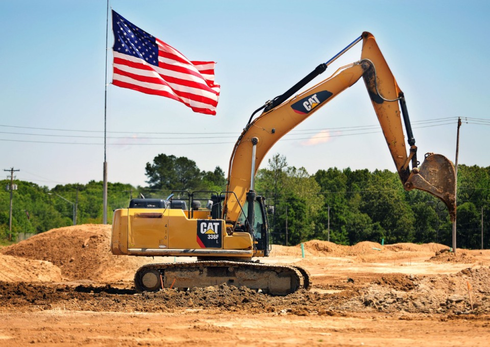 <strong>A flag waves (in a file photo) as a crane moves dirt at the Lake District mixed-use development in Lakeland.</strong> (Patrick Lantrip/Daily Memphian)