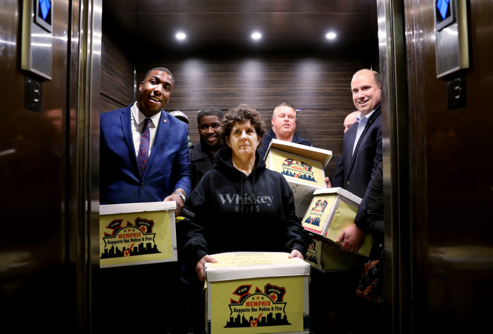 <strong>Holly Carter (center), a retired fire investigator, joins her colleagues as they take an elevator to the basement of City Hall to drop off a petition for a half-cent sales tax increase to restore benefits for police officers and firefighters while also funding road repairs and prekindergarten programs.</strong> (Houston Cofield/Daily Memphian)