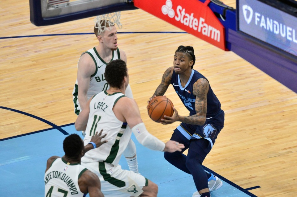 <strong>Grizzlies guard Ja Morant (12) eyes a shot as Milwaukee Bucks center Brook Lopez (11), guard Donte DiVincenzo (0) and forward Thanasis Antetokounmpo (43) close in&nbsp;on March 4 at FedExForum.</strong> (Brandon Dill/AP)