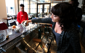 <strong>Alexandra Barnes, a bartender at The Greyhound inside the Hilton Garden Inn Memphis Downtown, practices serving drinks from the bar's menu. The hotel, which is set to open Thursday, Jan. 17, 2019, pays homage to the site's past as a Greyhound bus station.</strong> (Houston Cofield/Daily Memphian)