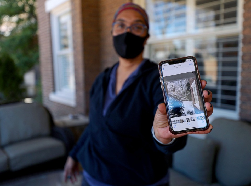 <strong>Denise Parker shows a picture of the ice that covered her house and garden last month on March 4, 2021</strong>. (Patrick Lantrip/Daily Memphian)