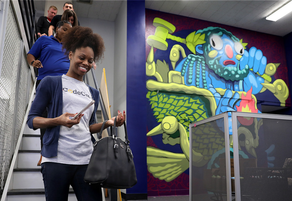 <strong>CodeCrew Code School program director Erin Johnson passes near a mural of Hephaestus during a tour of the former Highland branch library, which has been converted into a research incubator for the University of Memphis. The mural was created by local street artist and illustrator Michael Roy, who works under the moniker Birdcap.</strong> (Patrick Lantrip/Daily Memphian)