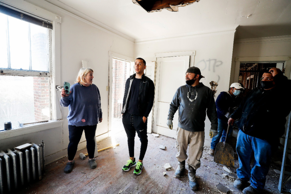 <strong>Cameron Ellis (middle), chats with subcontractor Charlene Williams (left) and her crew about ongoing renovations at one of his apartment buildings on Wednesday, March 3, 2021. Ellis, the 27-year-old owner of WeOffr, buys houses, renovates them and sells them now mostly to homeowner-occupants. He more recently added apartment buildings to his business.</strong> (Mark Weber/The Daily Memphian)
