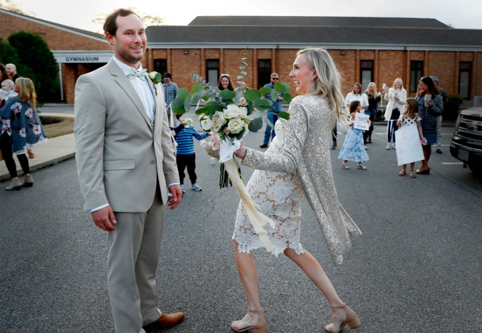 <strong>Just-married John Steinert and Holly Whittle celebrate with cheering friends who surprised them in the parking lot after their wedding on Saturday, March 21, 2020 at St. Louis Catholic Church.</strong> (Mark Weber/Daily Memphian file)
