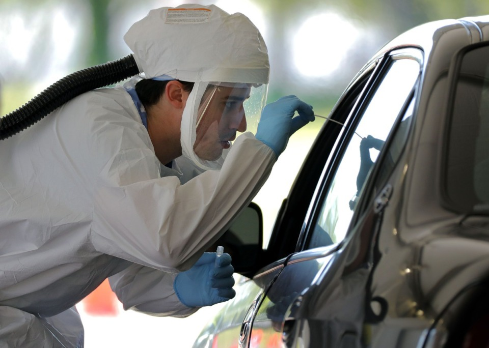 <strong>A UTHSC doctor swabs a patient during a drive-thru COVID-19 test at Tiger Lane April 10, 2020.</strong> (Patrick Lantrip/Daily Memphian file)