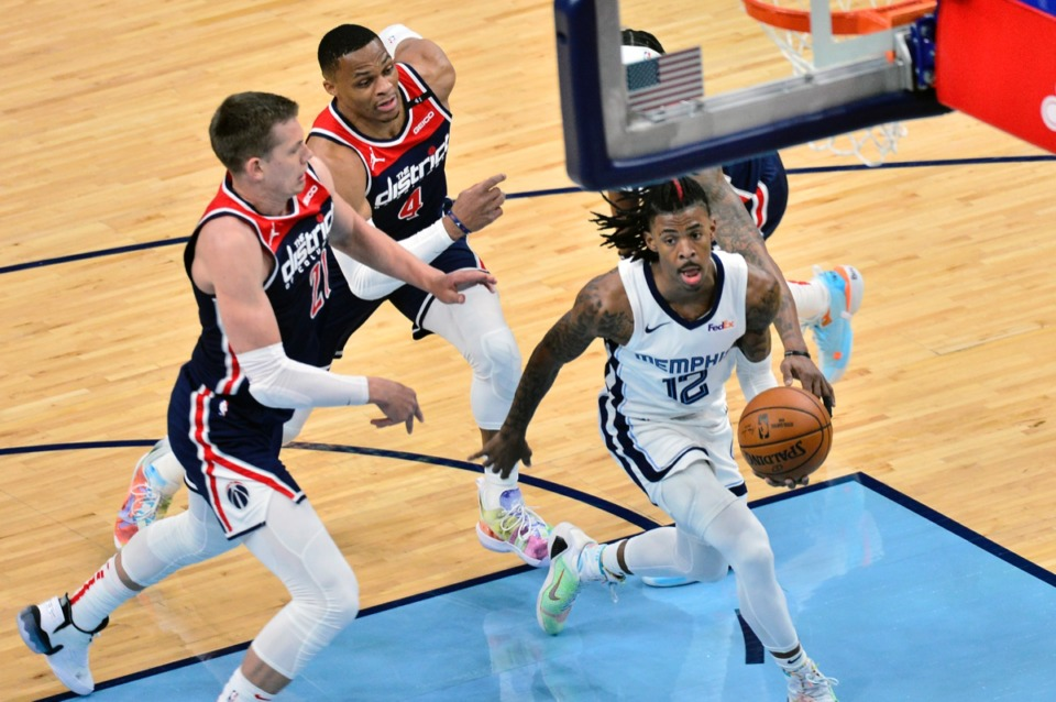 <strong>Grizzlies guard Ja Morant (12) drives ahead of Washington Wizards center Moritz Wagner (21) and guard Russell Westbrook (4)&nbsp;on March 10 at FedExForum.</strong> (Brandon Dill/AP)