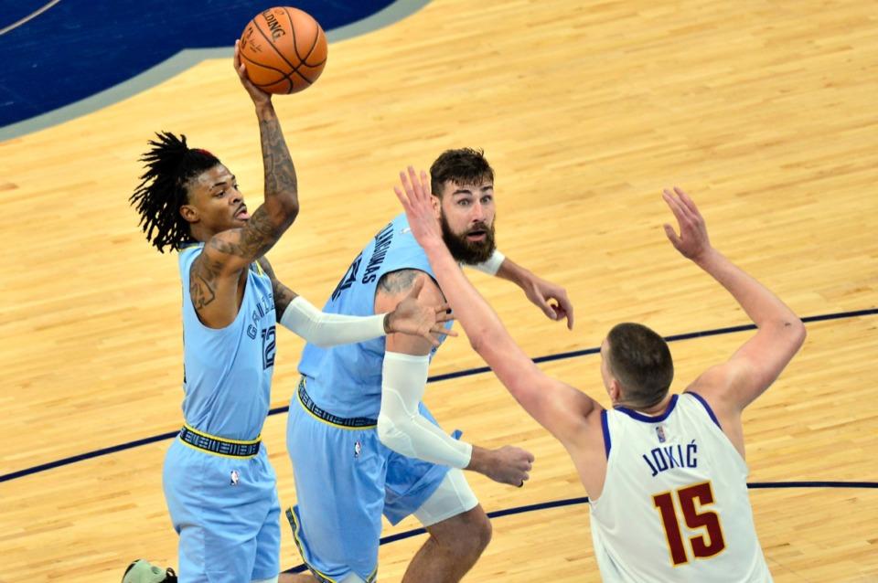 <strong>Memphis Grizzlies guard Ja Morant (12) shoots despite Denver Nuggets center Nikola Jokic (15) as center Jonas Valanciunas blocks</strong>&nbsp;<strong>on March 12 at FedExForum.</strong> (Brandon Dill/AP)