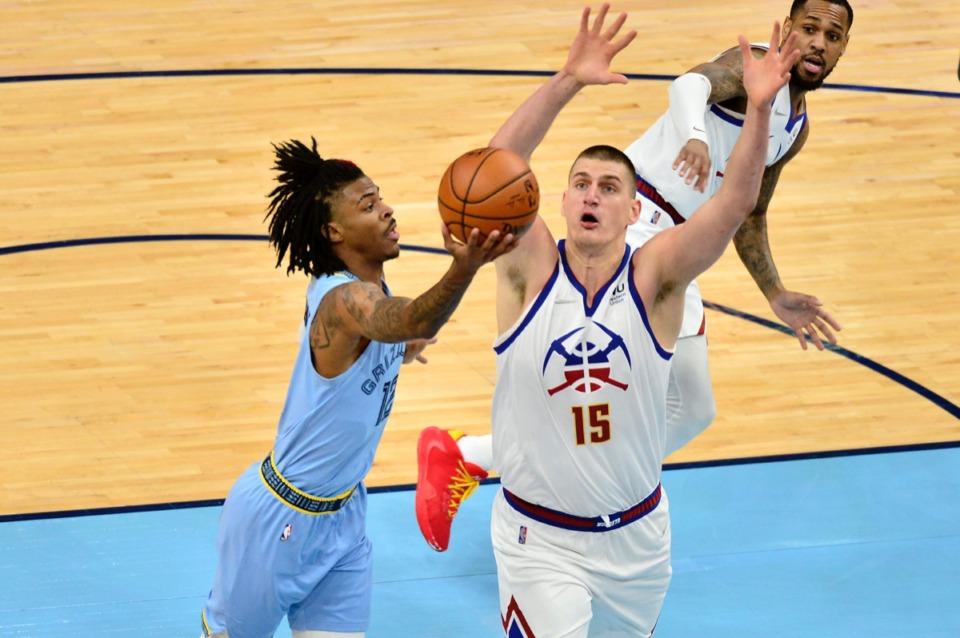 <strong>Memphis Grizzlies guard Ja Morant (12) shoots next to Denver Nuggets center Nikola Jokic (15)&nbsp;on March 12 at FedExForum.</strong> (Brandon Dill/AP)