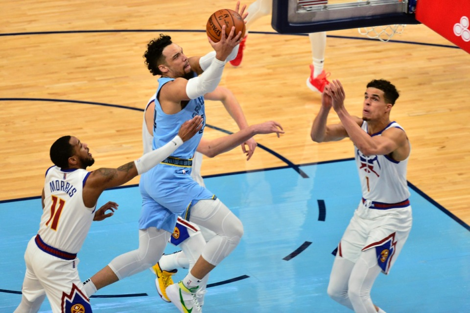 <strong>Memphis Grizzlies guard Dillon Brooks shoots between Denver Nuggets guard Monte Morris (11) and forward Michael Porter Jr. (1)&nbsp;on March 12 at FedExForum.</strong> (Brandon Dill/AP)