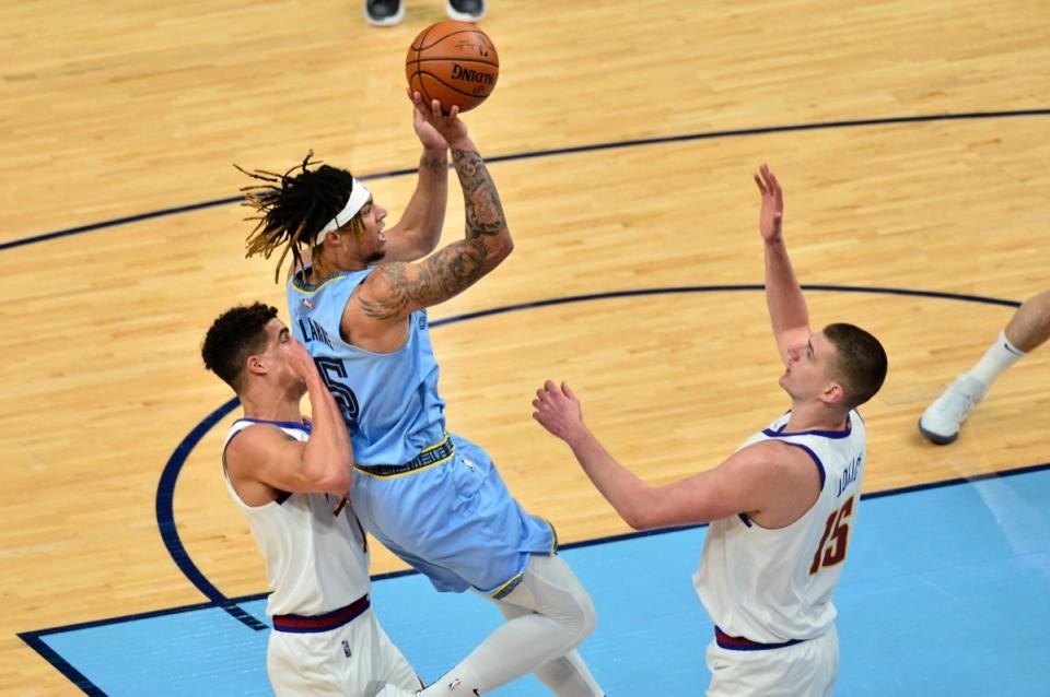 <strong>Memphis Grizzlies forward Brandon Clarke (15) shoots between Denver Nuggets forward Michael Porter Jr., left, and center Nikola Jokic&nbsp;on March 12 at FedExForum.</strong> (Brandon Dill/AP)