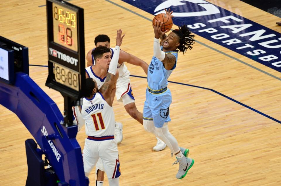 <strong>Memphis Grizzlies guard Ja Morant (12) shoots over Denver Nuggets guard Monte Morris (11)&nbsp;on March 12 at FedExForum.</strong> (Brandon Dill/AP)