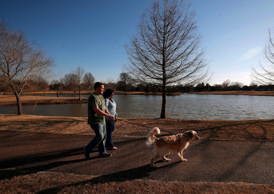 <strong>Ben and Jessica Jarratt walk their dog Remy around the lake at Davies Plantation Park, March 9, 2021.</strong> (Patrick Lantrip/Daily Memphian)
