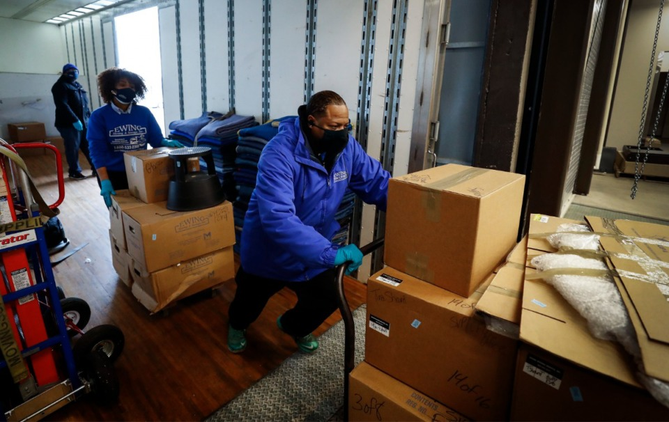 <strong>Samuel Ewing Jr. (right) and Zuri Elmore, while wearing face mask move boxes of office supplies into the new FedExLogistics building on Friday, Feb. 12, 2021</strong>. (Mark Weber/The Daily Memphian)