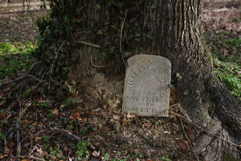 <strong>A loose headstone for William Brown leaning against a tree in Zion Christian Cemetery Tuesday, March 16, 2021.</strong> (Lucy Garrett/Special to the Daily Memphian)