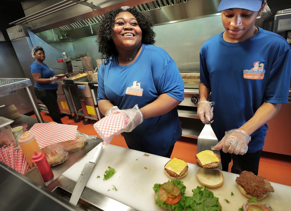 <strong>Mercades Fulton (center) and Kavonte Smith assemble burgers for the lunch crowd at the Wimpy's Burgers on Poplar Avenue in Midtown on Jan. 15, 2019. According to Wimpy's CEO Jacob Crafton, the local burger chain plans to open a third location in Germantown.</strong> (Jim Weber/Daily Memphian)