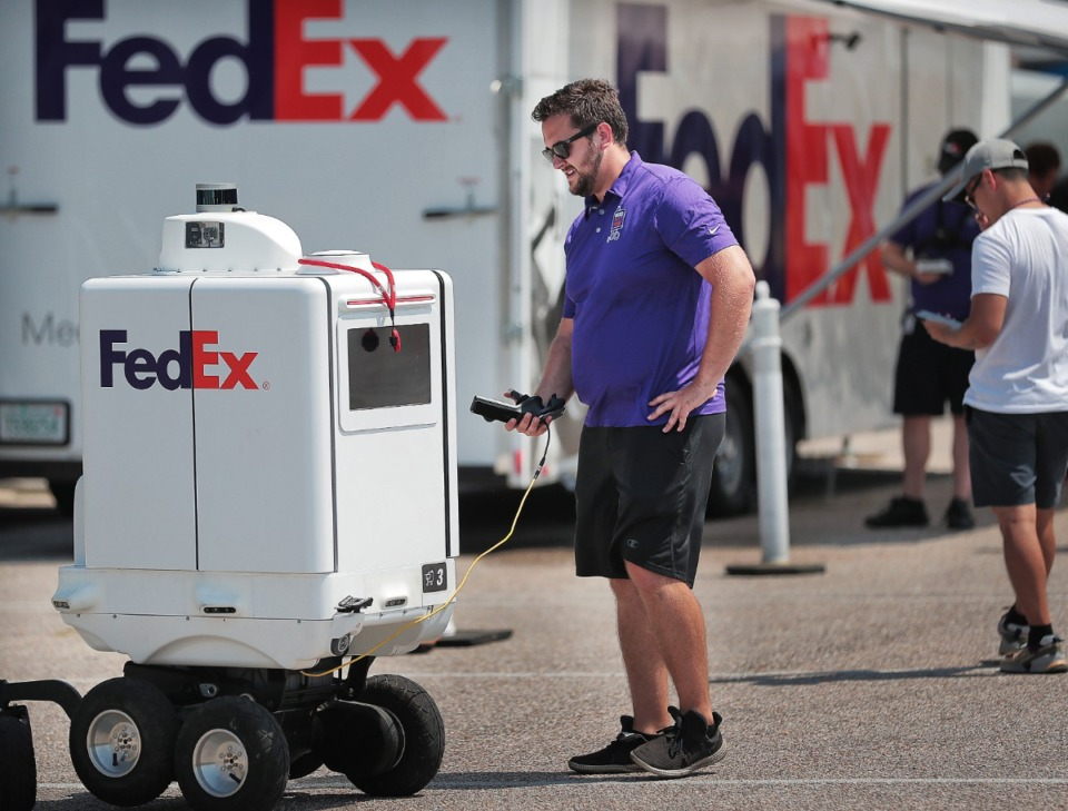 <strong>Richard DiPasquale, a member of the FedEx SameDay Bot test team, checks systems on Roxo before starting a test run at FedExForum on Sept. 4, 2019. FedEx is experimenting with environmentally friendly tools for short deliveries, such as battery-powered robots and drones.</strong> (Jim Weber/Daily Memphian file)