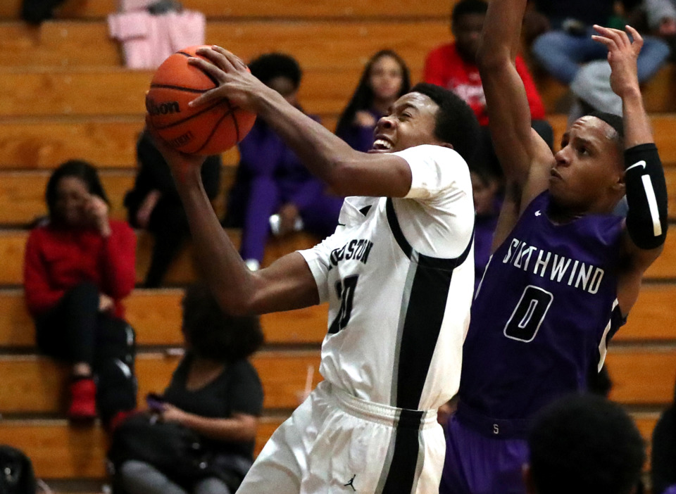 <strong>Houston High School guard T.J. Madlock (20) drives to the basket for a layup against Southwind High School guard Jeremiah Miller (0) during a game against Southwind on Tuesday, Jan. 15, 2019.</strong> (Houston Cofield/Daily Memphian)