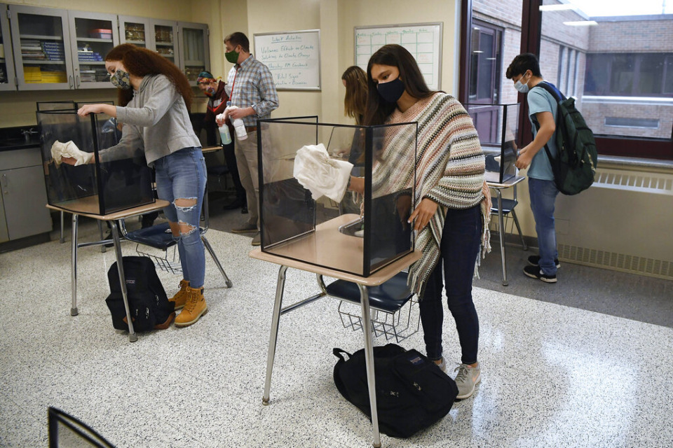 <strong>In this March 18, 2021, file photo, students in teacher Christopher Duggan's science class clean their work areas at the end of class at Windsor Locks High School in Windsor Locks, Connecticut.</strong> (AP Photo/Jessica Hill, File)